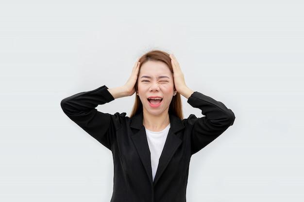 La donna asiatica frustrata di affari che grida e mette le mani sulla testa con capelli lunghi in vestito nero isolato su colore bianco