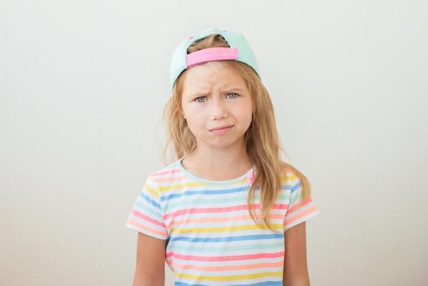 Bella bambina frustrata su bianco
