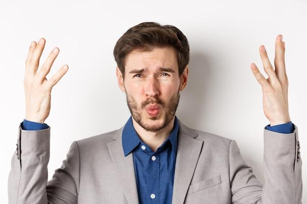 Uomo d'affari frustrato che stringe la mano e chiede a wtf cosa è successo, guardando deluso e scioccato alla telecamera, rimproverando il dipendente, sfondo bianco.