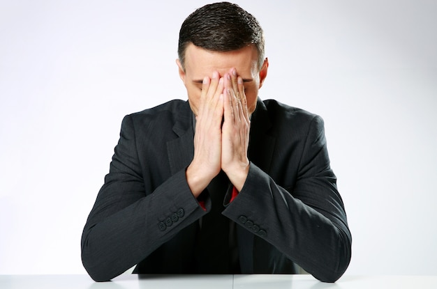 Uomo d'affari frustrato seduto al tavolo con le mani sul viso su sfondo grigio