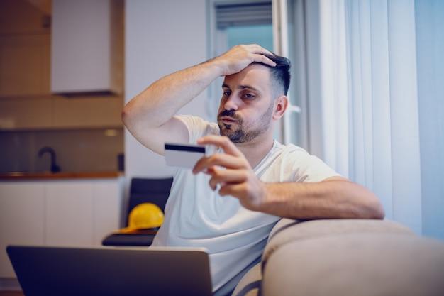 Uomo bello caucasico frustrato in pigiama che si siede nel salone con il computer portatile in grembo e carta di credito a disposizione.