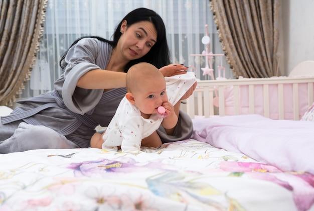 Una madre dall'aspetto frustrato in vestaglia che veste un bambino a casa in una stanza rosa con culla.