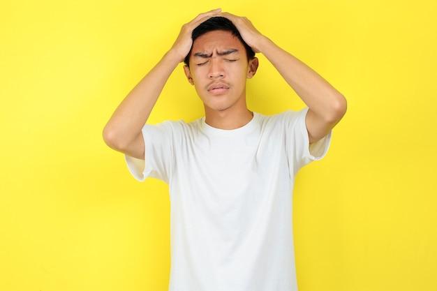 Uomo frustrato che tiene la sua testa. giovane uomo asiatico che fa il gesto di un uomo frustrato che si tiene la testa, isolato su sfondo giallo