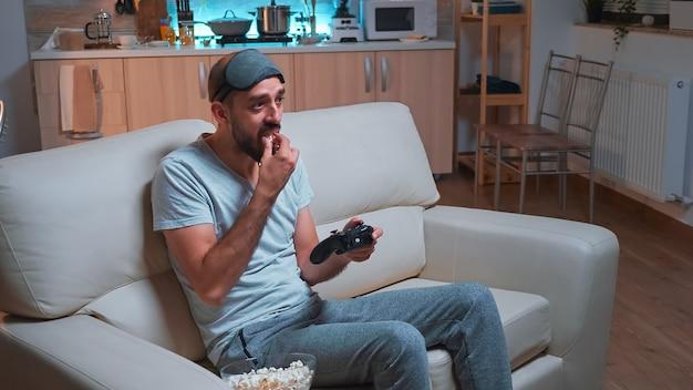 Uomo frustrato con la maschera per dormire che perde la competizione con i videogiochi