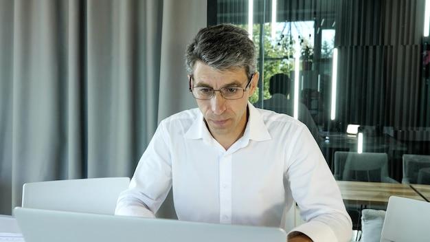 Impiegato frustrato, uomo d'affari utilizza il computer portatile