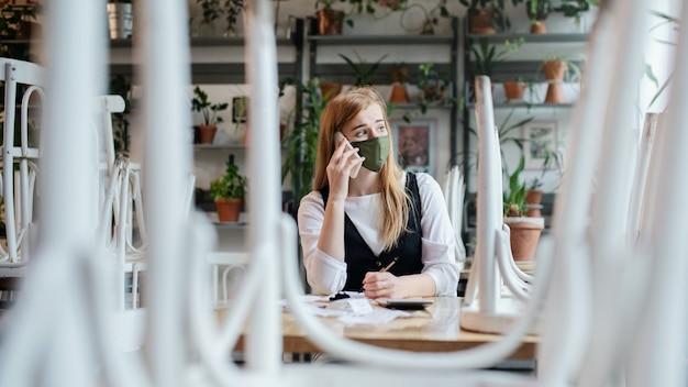 Proprietario frustrato seduto al tavolo in un bar chiuso o in una caffetteria?
