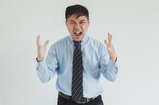 Uomo di vendita frustrato che indossa camicia blu e cravatta in posa con espressione arrabbiata e grida alla telecamera su sfondo bianco