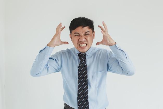 Uomo di vendita frustrato che indossa camicia e cravatta blu in posa con la faccia arrabbiata che guarda l'obbiettivo su sfondo bianco