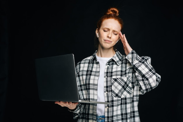 Giovane studentessa frustrata e stanca che ha un forte mal di testa mentre lavora al computer portatile