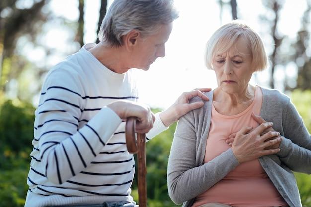 Donna anziana debole frustrata che si tocca il petto e ha un attacco di cuore mentre il marito anziano si preoccupa per lei e si siede sulla panchina all'aperto