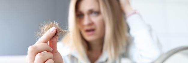 La donna frustrata tiene il panino dei suoi capelli nel suo concetto di perdita di capelli della mano
