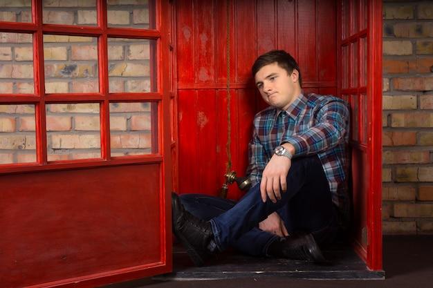 Frustrato giovane in attesa di una telefonata mentre si siede sul pavimento di una cabina telefonica pubblica accigliato infastidito
