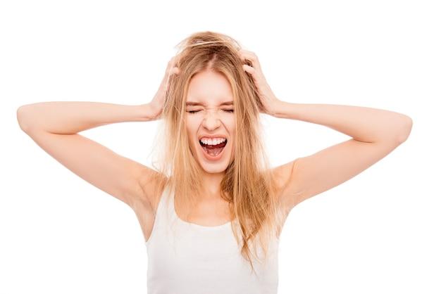 Giovane bionda graziosa frustrata con capelli danneggiati che grida