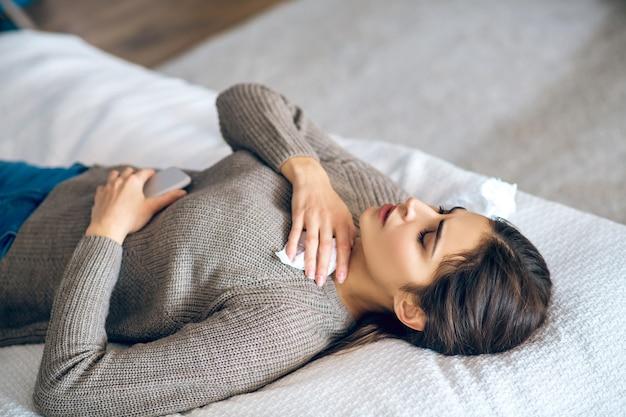 Frustrazione. giovane donna dai capelli scuri sdraiata sul letto con un telefono in mano e guardando frustrata