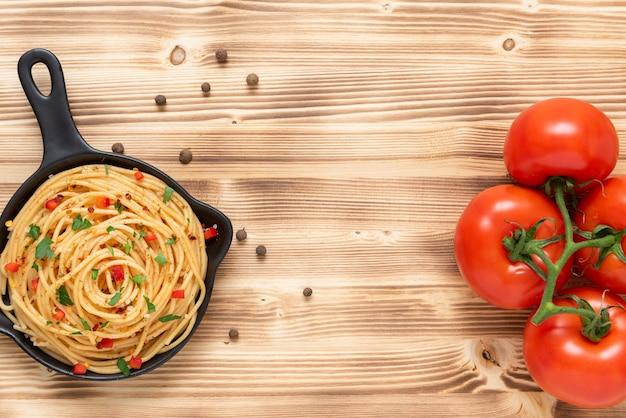 In una padella antiaderente, vermicelli con condimenti e pomodorini. copia spazio.