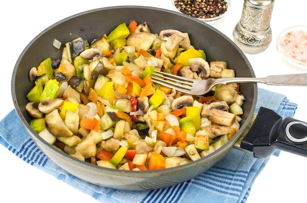 Padella con verdure di stagione fritte e funghi su bianco.