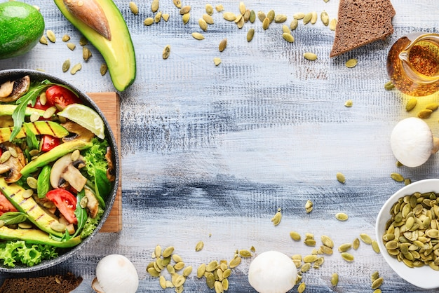 Padella con gustosa insalata di avocado e ingredienti su fondo in legno