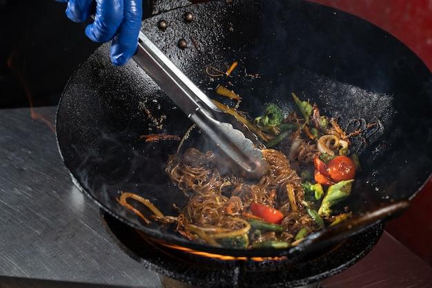Friggere le verdure in una padella wok cipolle, broccoli, pomodorini, carote, asparagi.