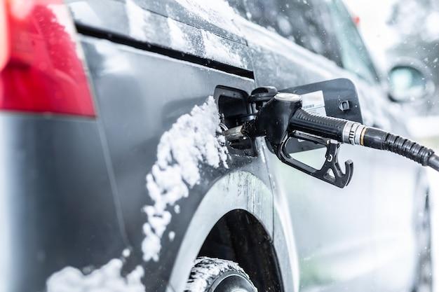 Pistola del carburante lasciata all'interno dell'auto durante il rifornimento di benzina o benzina alla stazione nel gelido inverno.