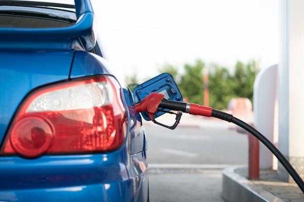 Una pompa del carburante inserita nell'auto sportiva sulla stazione di rifornimento, versa olio di benzina nel veicolo