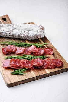 Fuet tagli interi e affettati, salsiccia stagionata spagnola su superficie bianca.