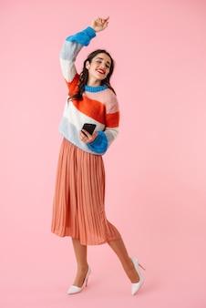 Ful lunghezza di una giovane e bella donna che indossa abiti colorati in piedi isolato su rosa, ascoltando musica con gli auricolari, tenendo il telefono cellulare