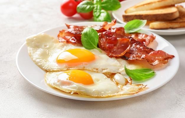 Colazione americana completa con uova fritte e pancetta arrosto su bianco.