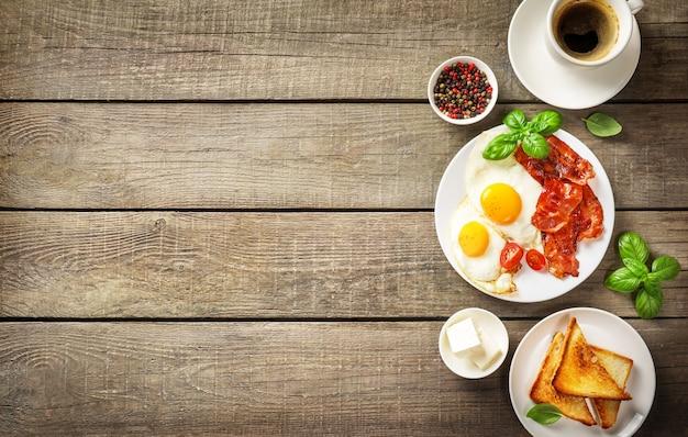 Colazione americana completa con uova fritte e pancetta arrosto su legno