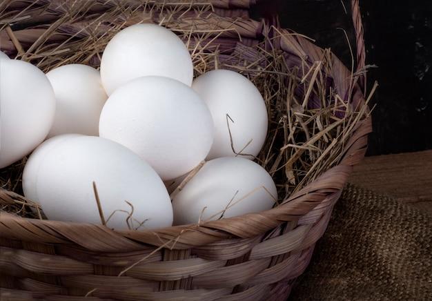 Un cesto pieno di uova di gallina con fieno su un tavolo rustico, primo piano.