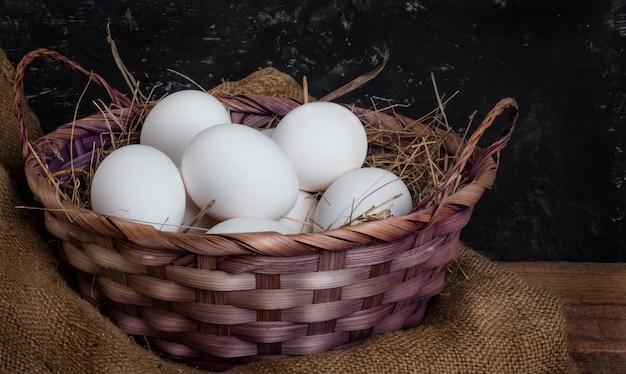 Un cesto pieno di uova di gallina con fieno su un tavolo rustico.