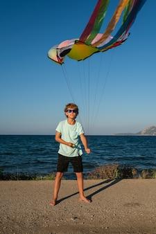 Corpo completo di ragazzo abbronzato attivo in occhiali da sole che tiene linee di aquiloni colorati che volano contro il cielo blu in una soleggiata giornata estiva in riva al mare