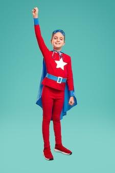 Ragazzo allegro di tutto il corpo in costume da supereroe che alza il pugno chiuso e sorride per la fotocamera mentre è pronto a salvare il mondo contro il turchese