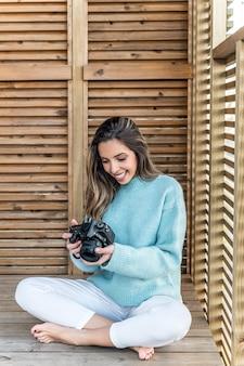 Corpo pieno di giovane donna a piedi nudi allegra in abiti casual con macchina fotografica in mano seduto sulla terrazza in legno
