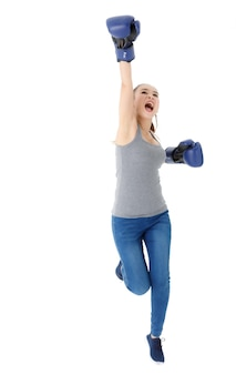 Corpo pieno di eccitata giovane donna energica in abito casual e guantoni da boxe che alzano le mani e saltano mentre celebrano il successo su sfondo bianco