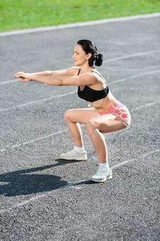 Corpo pieno di ragazza accovacciata sullo stadio, guardando da parte. profilo di ragazza in top nero, pantaloncini rosa e scarpe da ginnastica bianche che piegano le ginocchia, le mani davanti a lei. all'aperto, sport