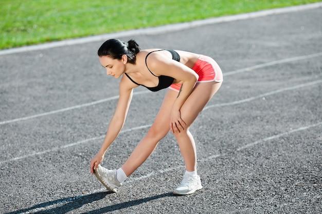 Tutto il corpo della ragazza in fase di riscaldamento prima di eseguire la pista. profilo di giovane donna in top nero, pantaloncini rosa e scarpe da ginnastica bianche che si piegano e si tirano la punta a se stessa. all'aperto, sport