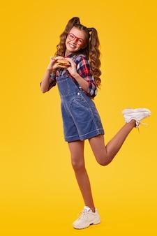 Corpo pieno di studentessa felice in tuta di jeans e scarpe da ginnastica che tengono hamburger e guardando divertendosi