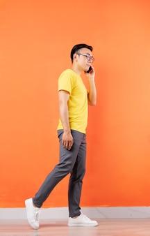 Foto di tutto il corpo dell'uomo asiatico in camicia gialla sulla parete arancione