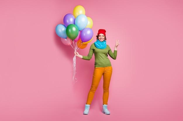 Foto di tutto il corpo di una ragazza allegra che tiene molti baloons d'aria fa il segno a v godere di occasioni per l'anniversario d'autunno indossare calzature stile casual pantaloni jumper isolate su muro di colore rosa
