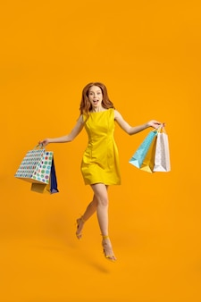 Foto a corpo intero di allegra signora turistica a piedi centro commerciale che trasporta molti pacchi, buon umore, i migliori fine settimana, saltare, indossare un abito isolato su sfondo giallo studio, ritratto