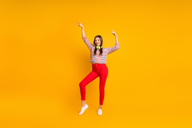 Foto di tutto il corpo della ragazza positiva allegra ascolta ballerino di ballo di musica canzone cuffia avricolare in festa indossare pantaloni rossi ponticello calzature isolate su un colore brillante