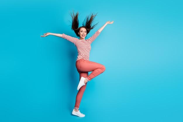 Foto completa del corpo di una ragazza entusiasta e sognante godetevi il fine settimana tempo libero alzate le mani indossate vestiti di bell'aspetto gumshoes shirt isolate su sfondo blu