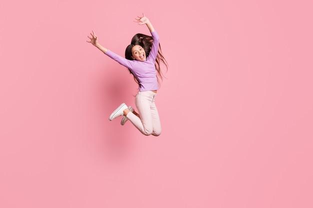 Foto a corpo intero di una ragazzina eccitata che salta alza le mani indossa scarpe da ginnastica maglione viola isolate su uno sfondo di colore pastello