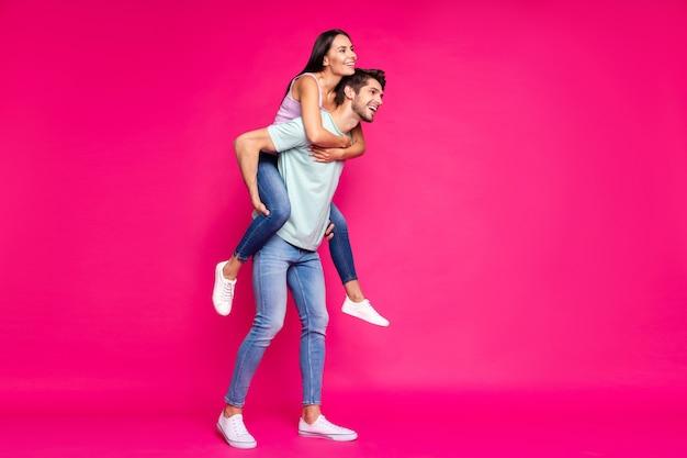 Foto di tutto il corpo di ragazzo divertente e signora che tiene sulle spalle passare il tempo libero guardando lontano indossare abiti casual isolato sfondo di colore rosa vibrante