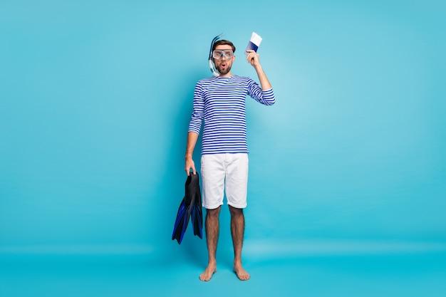 Foto di tutto il corpo del ragazzo divertente viaggio in yacht turistico che mostra patente subacquea tenere maschera subacquea pinne tubo di respirazione indossare pantaloncini camicia marinaio a strisce isolato colore blu