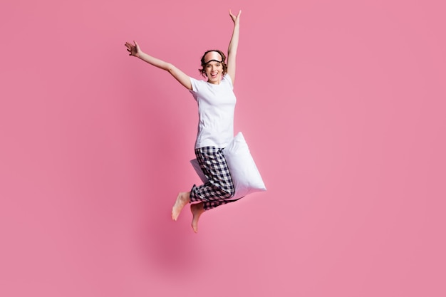 Foto di tutto il corpo della signora divertente saltare alto morbido grande cuscino tra le gambe