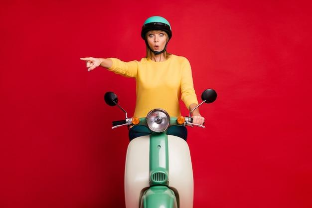 Foto di tutto il corpo del turista divertente signora che guida lo spazio vuoto del dito diretto della bici