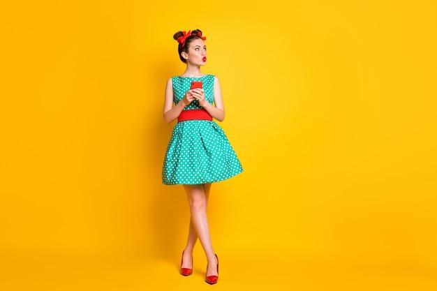 La foto del corpo intero della ragazza usa il cellulare guarda copyspace labbra carnose indossa gonna verde isolato sfondo di colore brillante