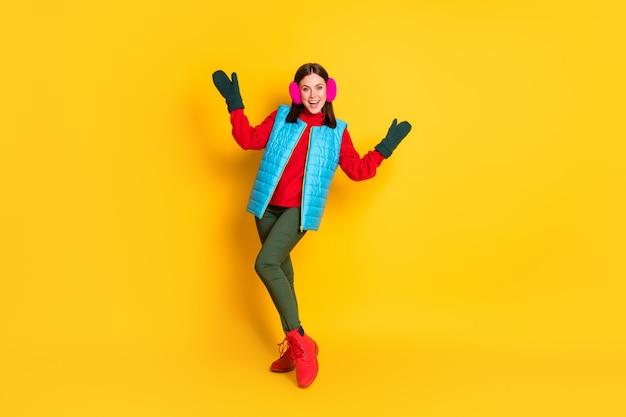 Foto completa del corpo di una ragazza di buon umore che si gode il maglione da indossare per le vacanze della stagione invernale isolato su uno sfondo di colore brillante