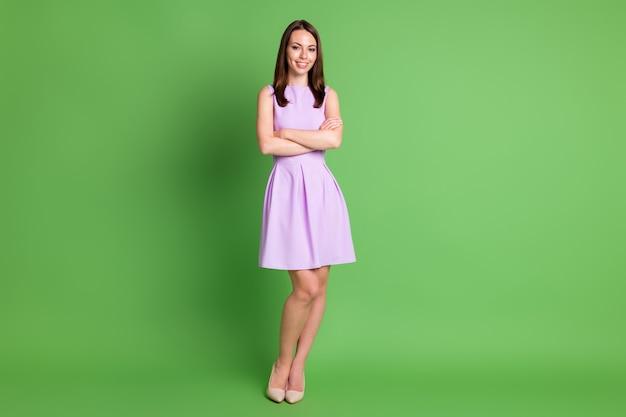 Foto completa del corpo della splendida ragazza sorridente signora mani incrociate gambe magre civettuolo stand posa annuncio reclutamento agenzia indossare abito viola scarpe beige isolato sfondo colore verde pastello